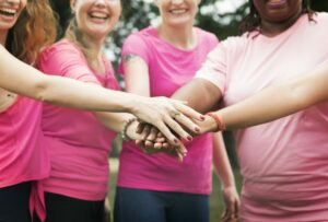 women in pink shirts touching hands