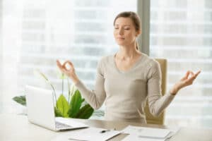 woman doing yoga pose at desk at work
