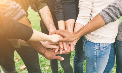 people in a group with hands gathered together in middle of group